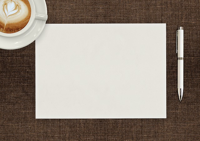 Coffee mug to the left of a landscape orientated piece of paper, with a white pen to the right.