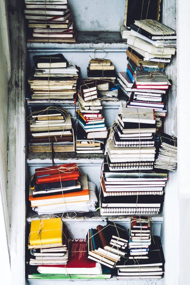 A pile of notebooks in various colours and sizes, arranged haphazardly in a cupboard under some stairs.